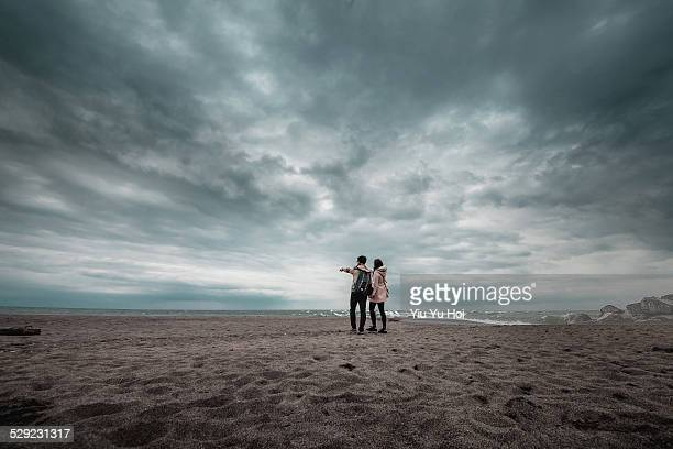 Romantic couple holding hands walking on beach