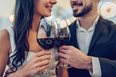 Cropped image of loving couple is spending time together in modern restaurant. Attractive young woman in dress and handsome man in suit are having romantic dinner. Celebrating Saint Valentine's Day.