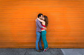 Romantic couple kissing in front of orange shutter