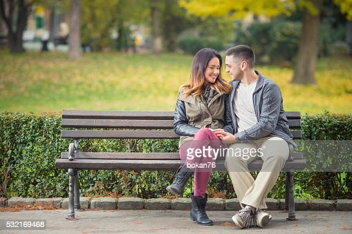 Romantic Couple On A Park Bench Stock Photo Thinkstock