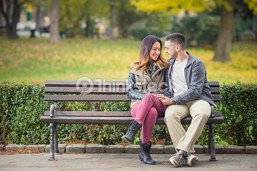 Romantic Couple On A Park Bench Stock Photo Thinkstock