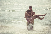 A young man is carrying a woman in his arms in a shallow water.