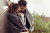 Romantic couple on a winter holiday. Man and woman standing together in a hotel room balcony wrapped in blanket. Couple embracing and smiling.
