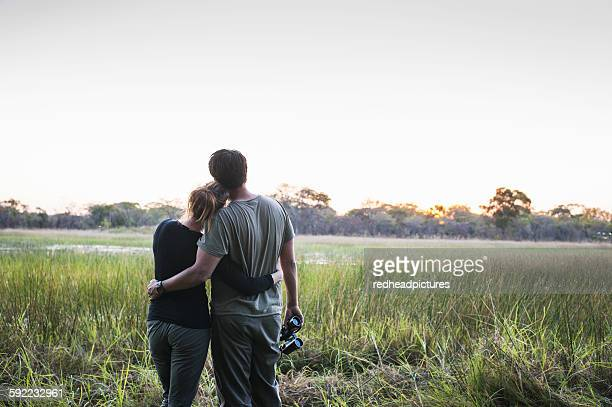 Romantic couple on safari looking out at landscape, Kafue National Park, Zambia
