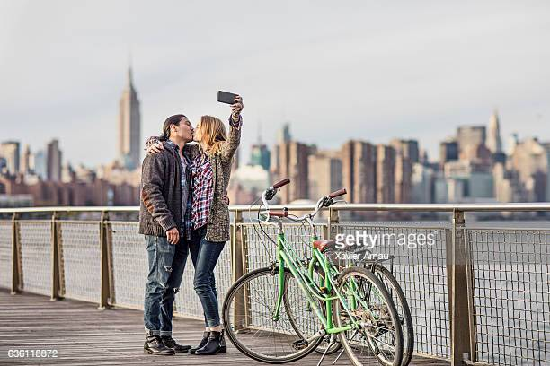 Romantic couple photographing against city skyline