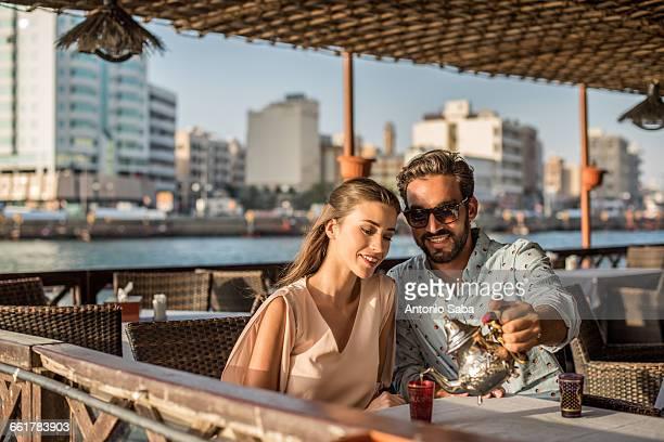 Romantic couple pouring tea at Dubai marina cafe, United Arab Emirates