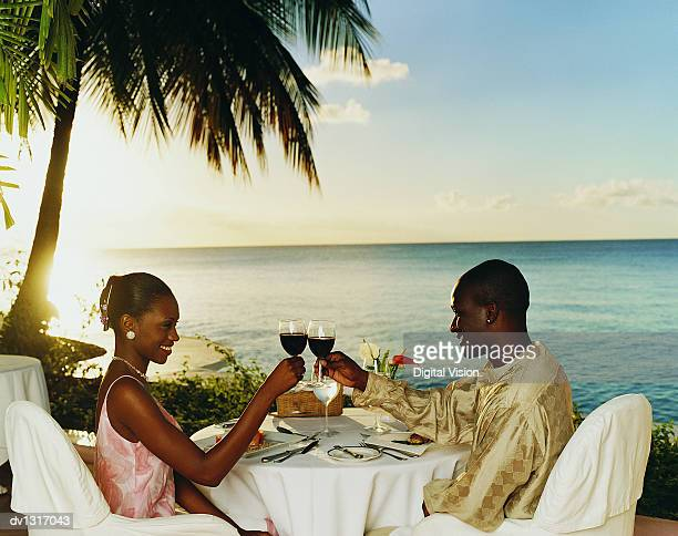 Romantic Couple Sitting in a Restaurant on the Coast at Sunset toasting With Glasses of Red Wine