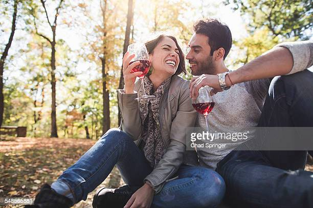 Romantic couple sitting in forest drinking rose wine