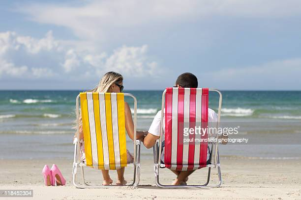 Romantic couple sitting on beach chairs