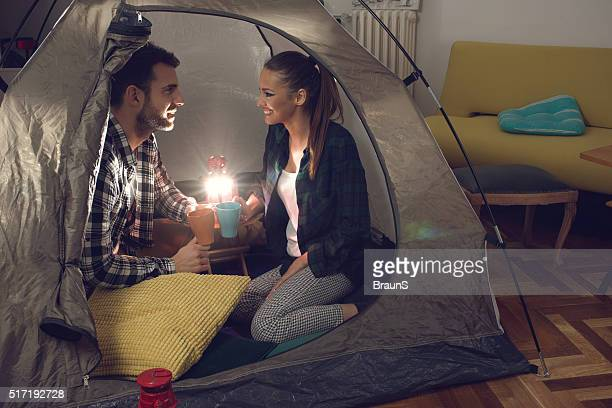 Romantic couple talking to each other during camping at home.