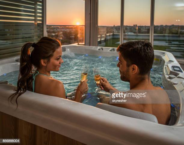 Romantic couple toasting with champagne while relaxing in a hot tub.