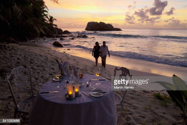 Romantic couple walking at sunset on beach with dinner table in foreground.Cousine Island.Seychelles