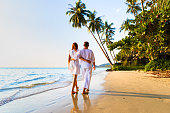 Romantic couple walking together on the tropical beach in warm sunny summer during honeymoon vacations