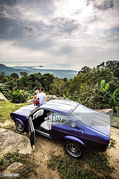 Romantique couple regardant le coucher de soleil assis dans la voiture