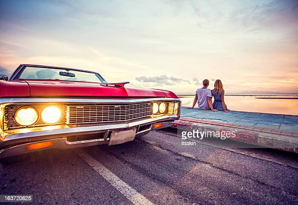 Romantic couple watching sunset with retro car