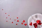 Romantic dinner decoration with cutlery and many red hearts and bow on gray table