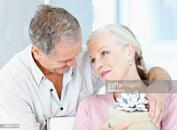 Romantic elderly man giving a giftbox to his wife