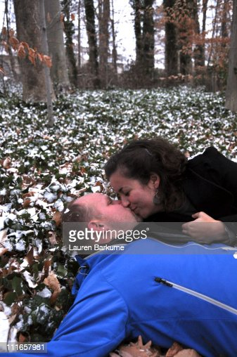 Romantic engaged couple kiss in snowy forest