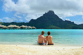 A honeymoon couple sharing a cocktail on the sand beach of a luxury vacation resort in the lagoon with a view on the tropical island of Bora Bora, near Tahiti, in French Polynesia.