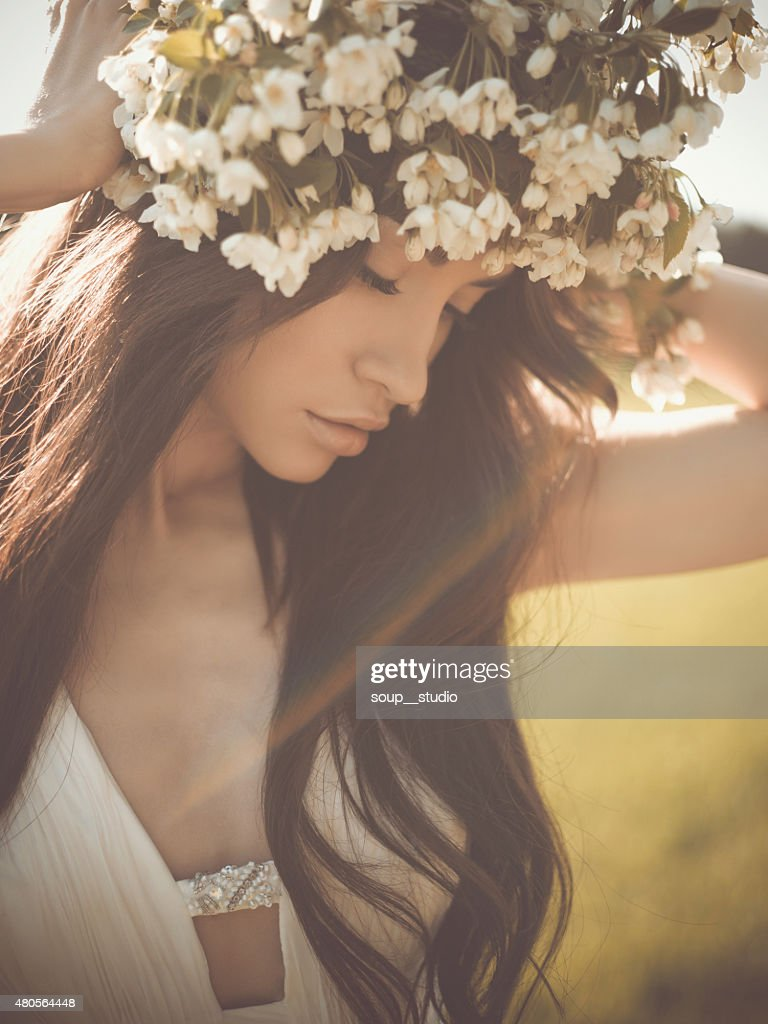 Romantic lady in a wreath of apple trees : Stock Photo