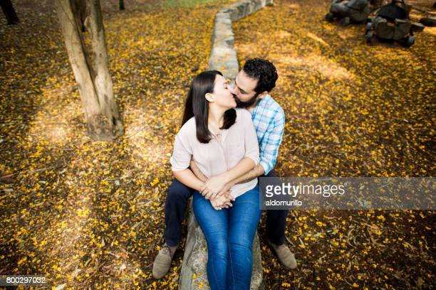 Romantic latin couple sitting and kissing on short wall
