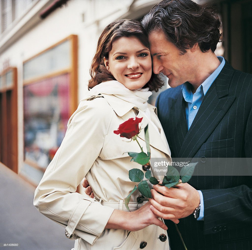 Romantic Man With His Arm Around a Woman on a City Pavement Giving Her a Red Rose : Stock Photo