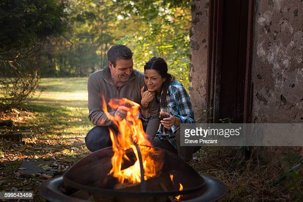 Romantic mature couple crouching by garden campfire