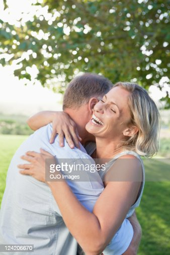 Romantic mature couple embracing each other in the park : Stock Photo