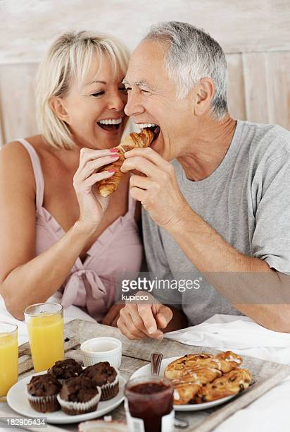 Romantic mature couple enjoying their breakfast in bed