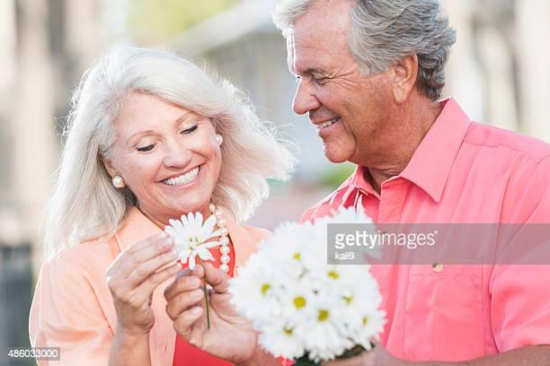 Romantique couple d'âge mûr avec bouquet blanc de pâquerettes