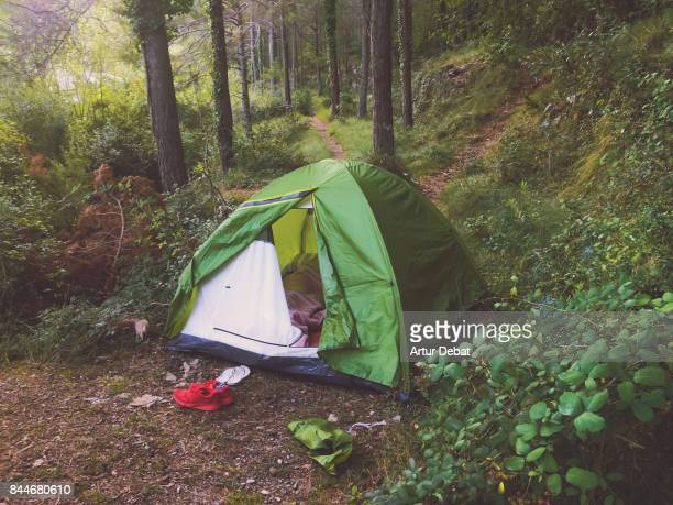 Romantic morning of couple doing camping with green tent between the beautiful nature forest in the Catalonia region during summer travel in the mountains.