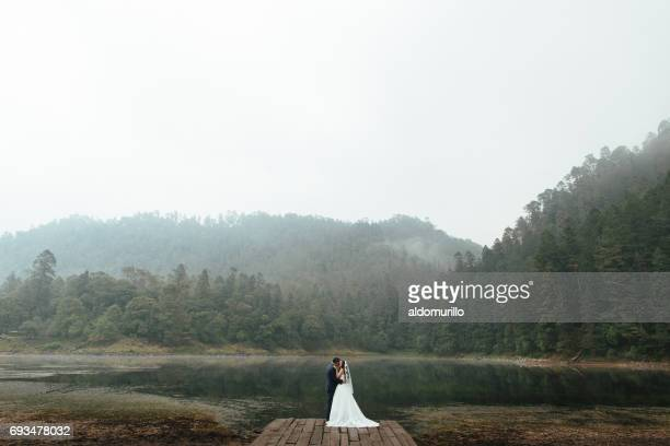 Romantic newlyweds kissing outdoors in foggy day