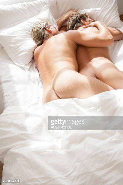Romantic nude male couple asleep on bed
