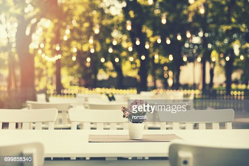romantic outdoor restaurant in park with string lights at sunset : Stock Photo