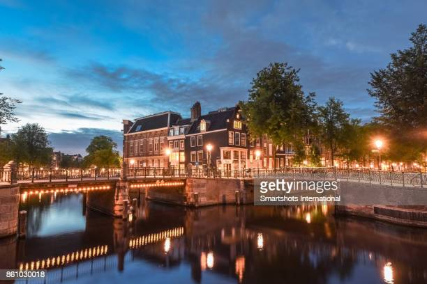 Romantic reflection of illuminated  bridges on quiet canal at dusk in Amsterdam, The Netherlands, a UNESCO Heritage site