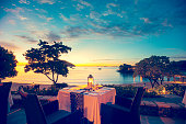 A table for two at a beach restaurant. The table is right on the beach at sunset with a lovely view of the water. Table is set for several courses with white table cloth. Absolute waterfront with lapp