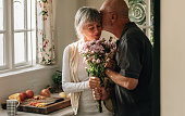 Senior couple standing in kitchen holding a bunch of flowers. Senior man kissing his wife holding her hand at home.