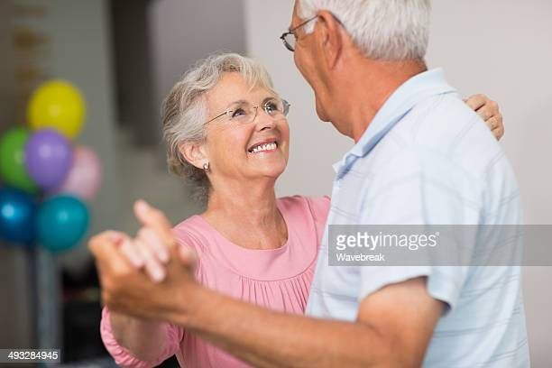 Romantic senior couple dancing at home