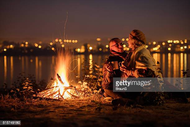 Romantic senior couple relaxing in the night by the fire.