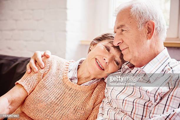 Romantic senior couple reminiscing on sofa