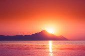 Beautiful vibrant sunrise over sea behind mountain