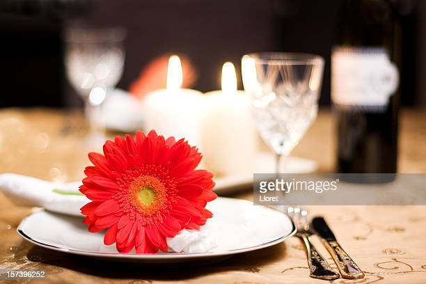 A romantic table for two with a red flower