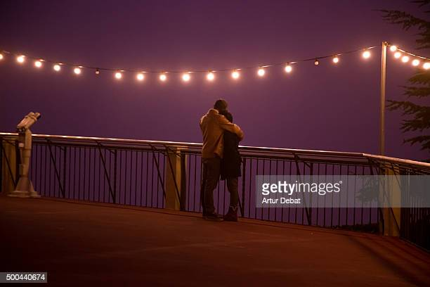Romantic view of a couple in the Tibidabo viewpoint in a winter foggy night.