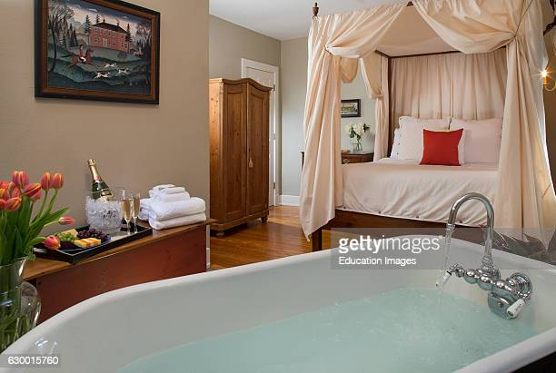 Romantic view of claw foot tub and bed in guest room Fife Drum Inn Williamsburg VA