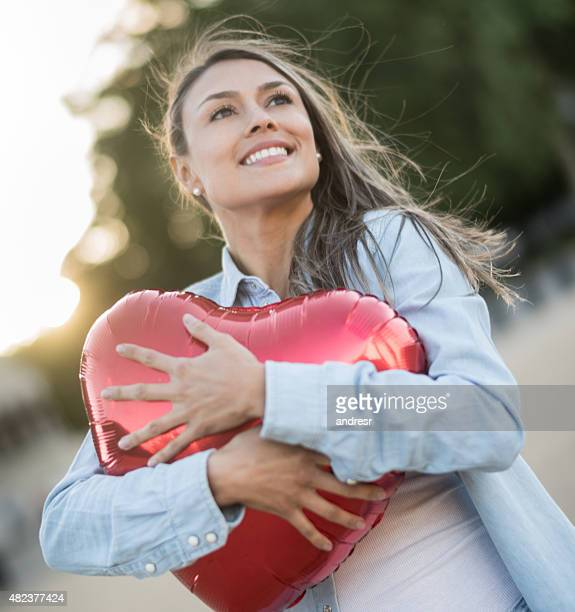 Romantic woman holding a red helium balloon