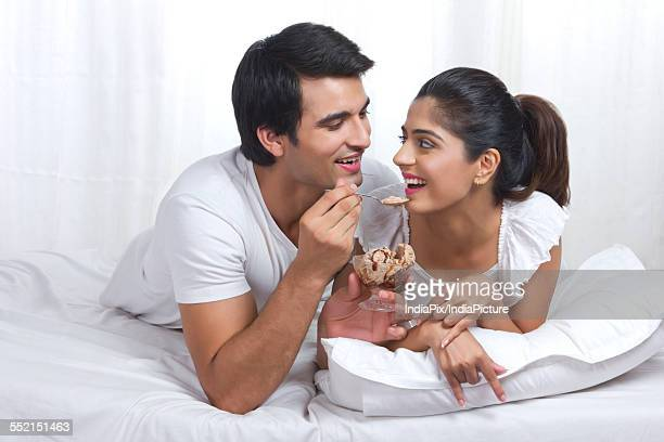 Romantic young couple enjoying chocolate ice-cream in bed