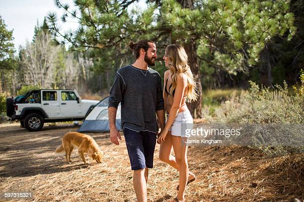 Romantic young couple holding hands in forest campsite, Lake Tahoe, Nevada, USA