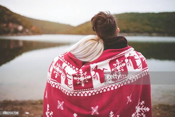 Romantische junge Paar umarmen am See im Herbst