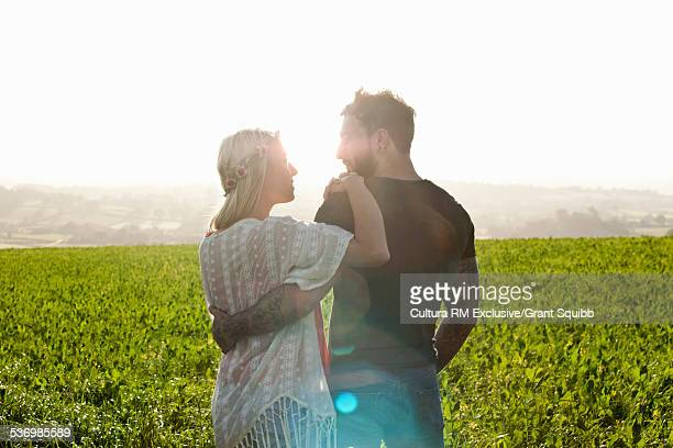Romantic young couple in rural field, Dorset England
