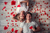 Top view of beautiful young couple holding red paper hearts, looking at camera and smiling while lying on the floor